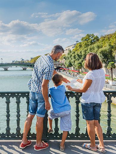 Family of three on bridge in Paris, France