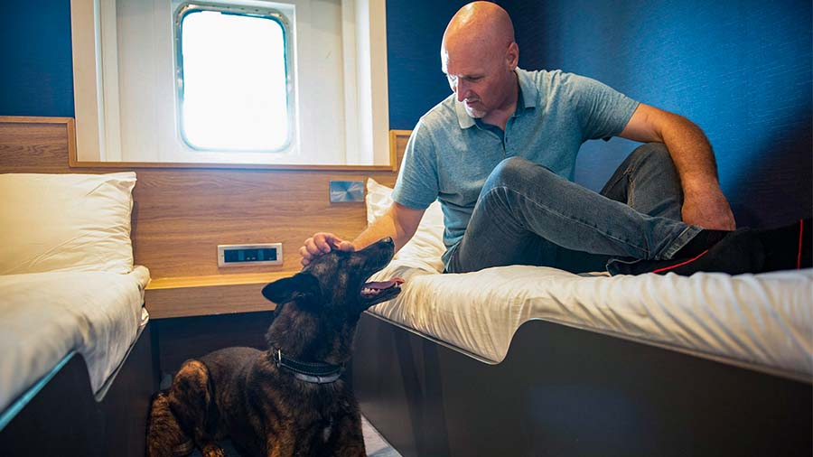 Dog with owner in a P&O Ferry dog cabin