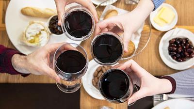 Brasserie wine bar - quatre personnes tenant haut un verre de vin rouge