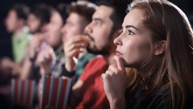 Cinéma - rangée de personnes regardant un film avec leur pop-corn