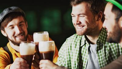 Irish bar - trois amis buvant une pinte de bière au bar