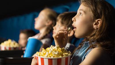 Kinderfilms - rij kinderen met popcorn die naar een film kijken