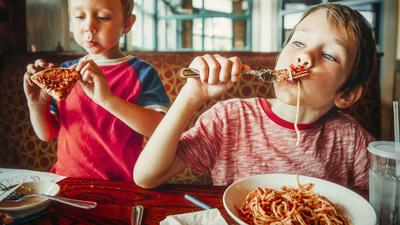 L'heure du dîner pour les enfants - deux enfants mangent des spaghettis