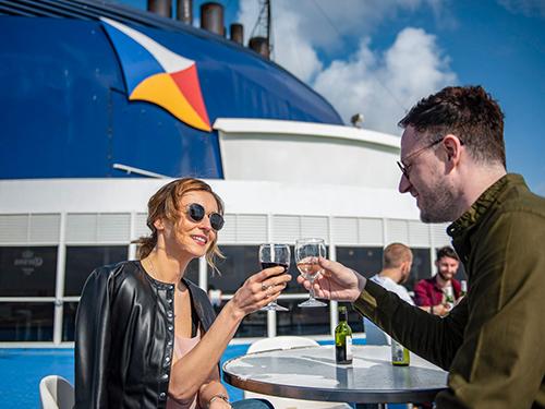 couple enjoying drinks on sun deck of P&O ferry
