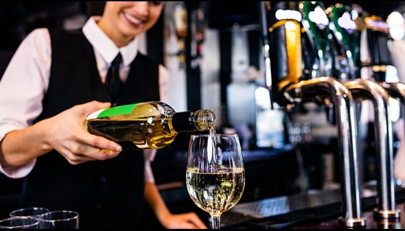 Bar - woman pouring glass of white wine at a bar