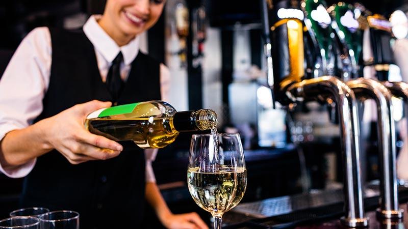 Bar – Frau schenkt sich ein Glas Weißwein an der Bar ein