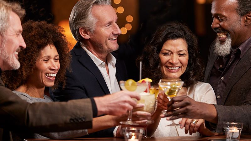Sunset Show Bar – Männer und Frauen im mittleren Alter genießen Cocktails in einer Bar