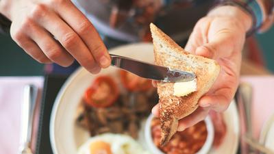 Food Court - ontbijt met iemand die boter op zijn toast smeert