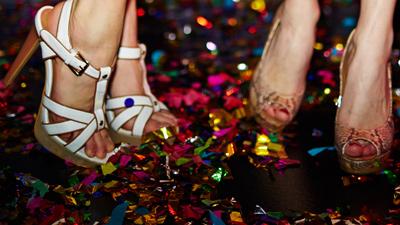 Sunset Show Bar – Nahaufnahme von zwei tanzenden jungen Frauen in hohen Schuhen mit Konfetti