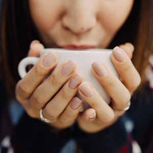 Lady sipping hot drink in coffee shop