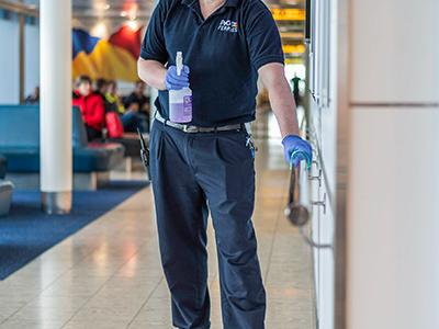 P&O staff member disinfecting hand rail